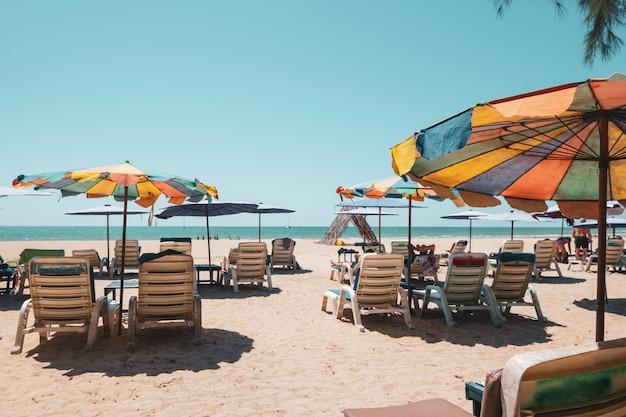 Camas de sun na praia tropical com céu calmo. opinião do mar e praia da areia, fundo do verão.