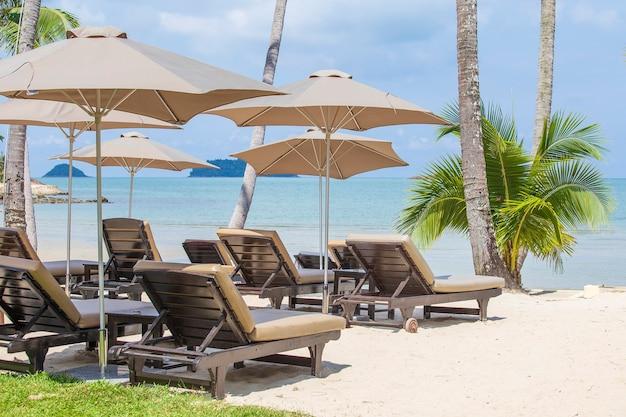 Camas relaxantes e guarda-sol em uma praia de areia tropical perto do mar na tailândia