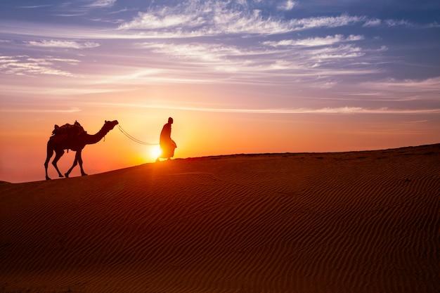 Cameleiro indiano beduíno com silhuetas de camelo nas dunas de areia do deserto de thar, no pôr do sol.