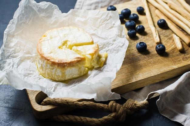 Camembert cozido francês com mirtilos e biscoitos.