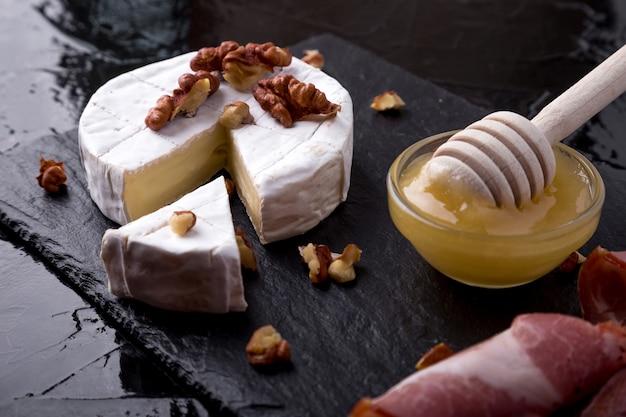 Camembert de queijo com nozes e honyey na placa de ardósia preta.