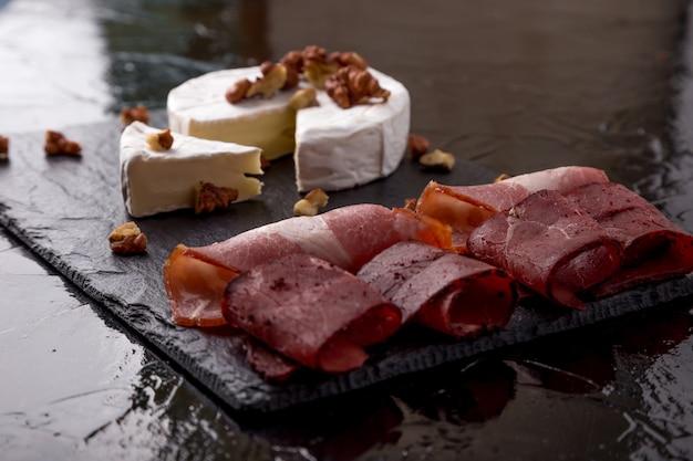 Camembert de queijo com nozes e prato de carne com nozes na placa de ardósia preta.