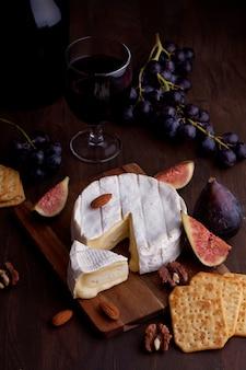 Camembert de queijo francês com copo de vinho tinto, uvas e figos