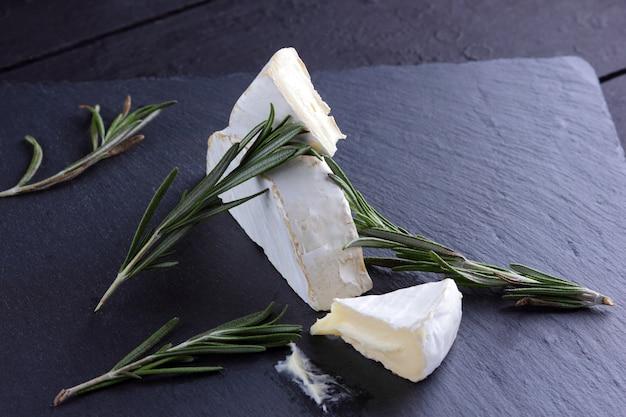 Camembert e alecrim na placa de pedra preta. queijo com mofo branco sobre fundo preto. fatias de queijo e alecrim ramos na placa de ardósia