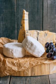 Camembert e queijo azul stilton com uvas. prato de queijo em fundo de madeira