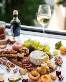 Camembert, queijo parmesão, presunto e variedade de frutas com copo de vinho branco