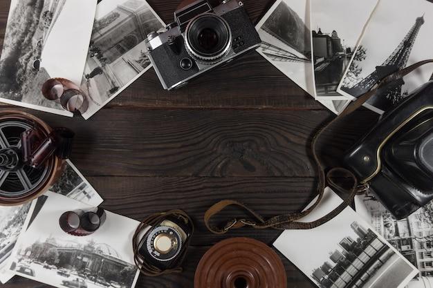 Câmera antiga, acessórios e fotografias em preto e branco estão na superfície de madeira escura em estilo retro