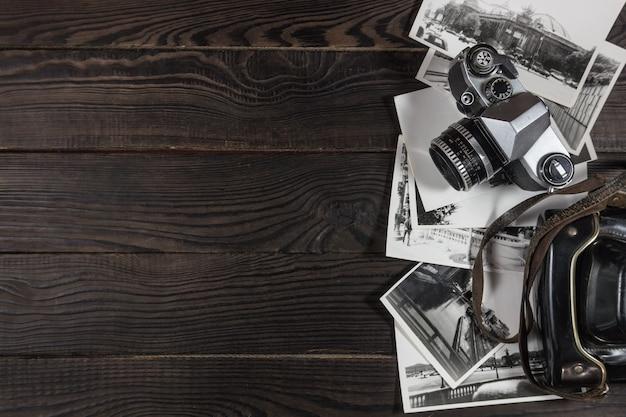 Câmera antiga, acessórios e fotografias em preto e branco estão na superfície de madeira escura. retro. vista do topo