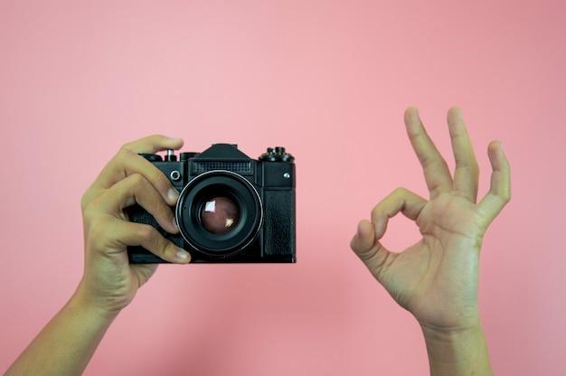 Câmera antiga em mãos femininas em um fundo rosa
