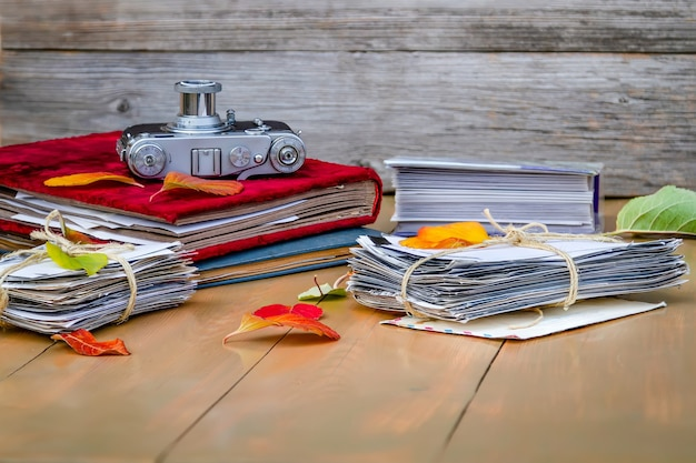 Câmera antiga, fotos em uma pilha, folhas de outono, óculos, álbum de fotos em uma mesa de madeira.