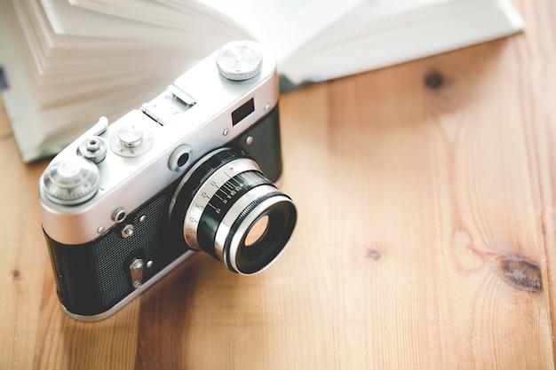 Câmera antiga vintage com livro em uma mesa de madeira