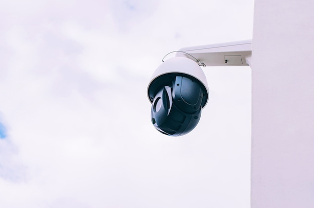 Câmera cctv na parede da casa. no contexto do céu.
