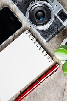 Câmera clássica com a página vazia do bloco de notas e a pena vermelha em de madeira cinzenta, mesa do vintage com telefone.