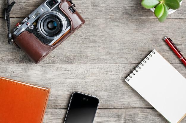 Câmera clássica com a página vazia do bloco de notas e a pena vermelha na tabela cinzenta de madeira, do vintage com telefone e a flor verde. caderno marrom.