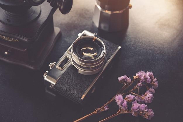 Câmera clássica na blackground de cor preta com flor roxa seca