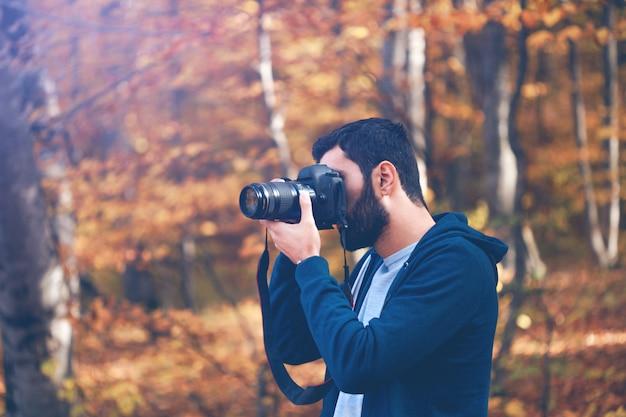 Câmera com a mão do fotógrafo na floresta de outono