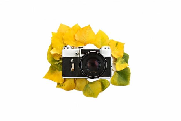 Câmera com lente em folhas de outono coloridas no centro. brincar. isolado no branco