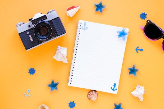 Câmera com óculos escuros, conchas e caderno em branco
