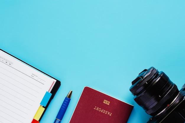 Câmera com passaporte, caderno e caneta sobre fundo azul para viagens e conceito de planejamento