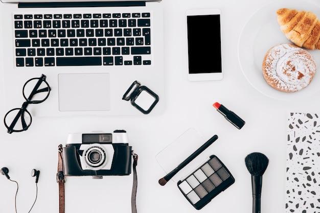 Câmera; computador portátil; celular; produto de cosméticos e pastelaria assada na mesa branca