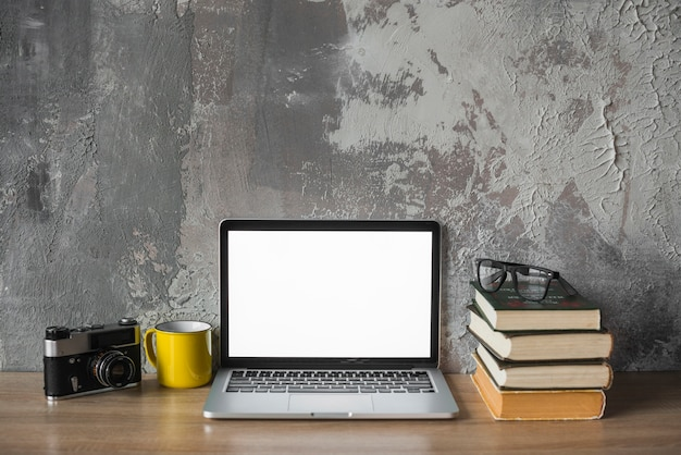 Câmera; copo; livros empilhados; óculos e laptop com tela branca em branco na mesa de madeira