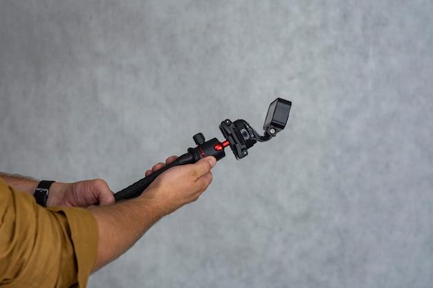 Câmera de ação compacta em um tripé flexível na mão sobre um fundo claro.