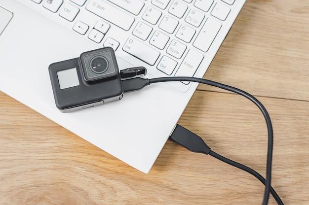 Câmera de ação conectada a um laptop branco