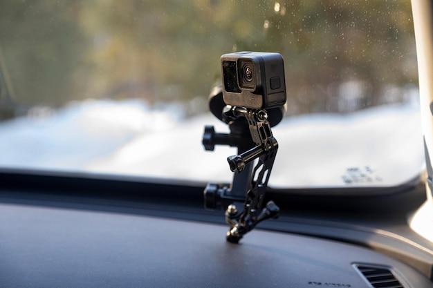 Câmera de ação em um suporte preso ao para-brisa do carro filmando em movimento