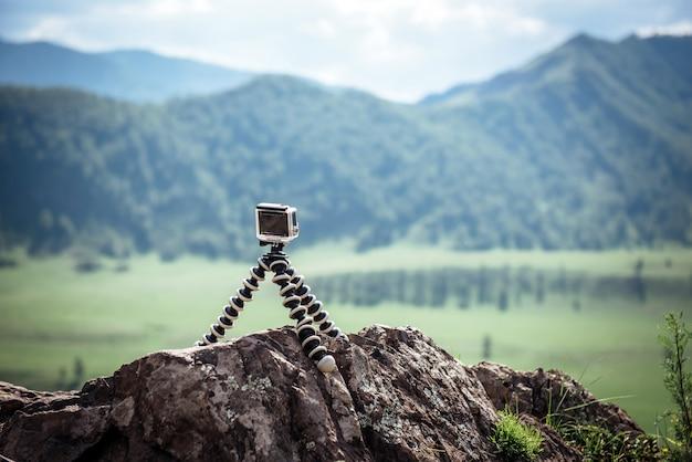 Câmera de ação fica em um tripé portátil em uma pedra