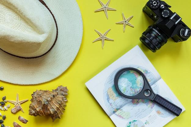 Câmera de acessórios de viagem, chapéu de palha, cartão, sapatos em um layout de vista superior plana de fundo amarelo com espaço de cópia