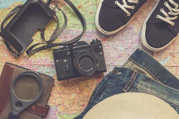 Câmera de acessórios de viagem, chapéu de palha, cartão, sapatos, laptop, em um layout de vista superior plana de fundo escuro