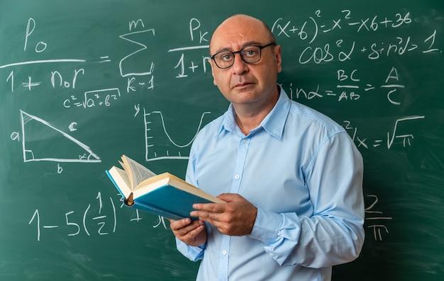 Câmera de aparência confiante, professor de meia-idade usando óculos, parado na frente do quadro-negro segurando um livro