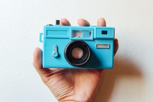 Câmera de brinquedo na mão em um fundo branco