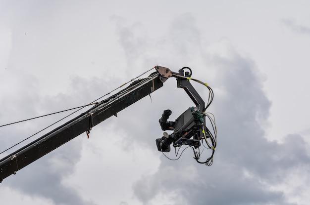 Câmera de cinema e televisão suspensa em um guindaste de transmissão com o céu nublado ao fundo.