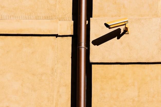 Câmera de circuito fechado de televisão (cftv) em uma parede amarela de um prédio. conceito de segurança.
