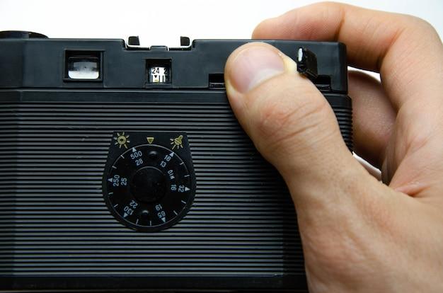 Câmera de filme antigo. câmera de raridade. uma câmera nas mãos de musa, inclinando. equipamento fotográfico soviético. a câmera em macro, lente, interior, detalhes