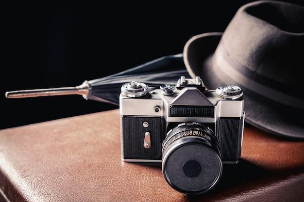Câmera de filme antigo com chapéu vintage e guarda-chuva na velha mala marrom