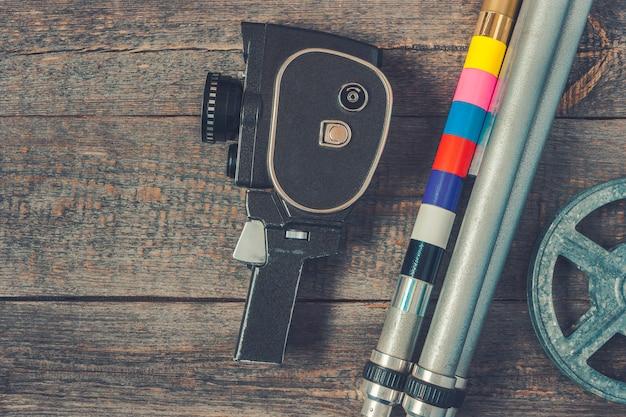 Câmera de filme antigo, tripé e rolo de filme