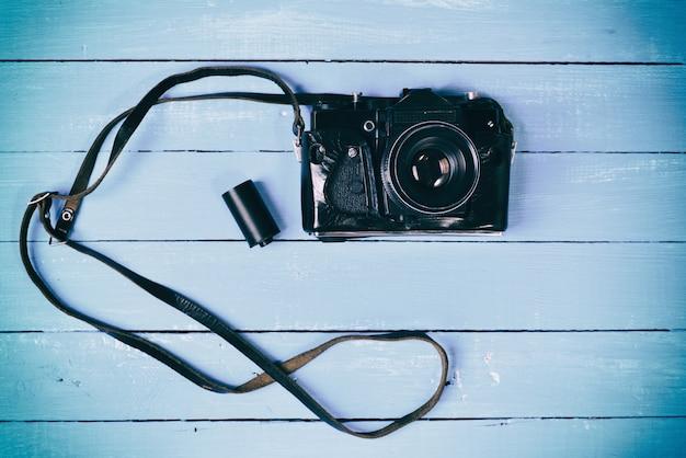 Câmera de filme retrô em uma superfície de madeira azul