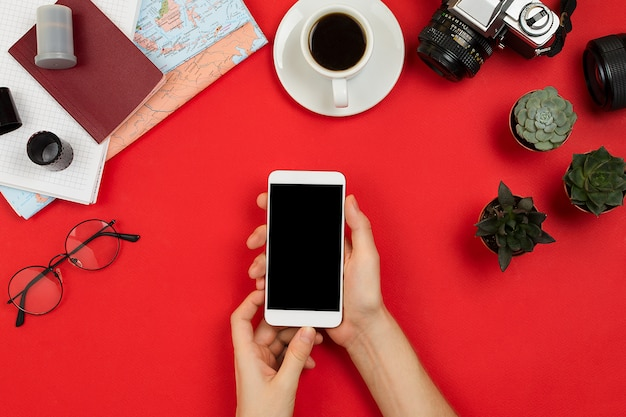 Câmera de filme vintage, lente, óculos, café, caderno, mapa e mãos de mulher segurando um smartphone