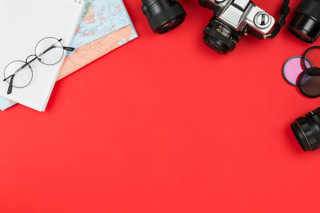 Câmera de filme vintage, várias lentes, óculos, caderno e mapa