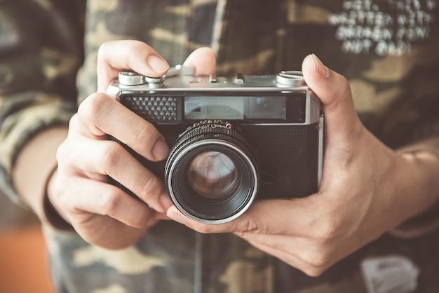 Câmera de foto vintage nas mãos do homem, foco suave.
