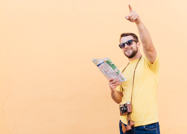 Câmera de fotógrafo branco jovem viajante bonito em volta do pescoço, apontando em algum lugar, mantendo o mapa