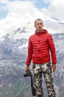 Câmera de fotógrafo masculino nas montanhas de mãos elbrus