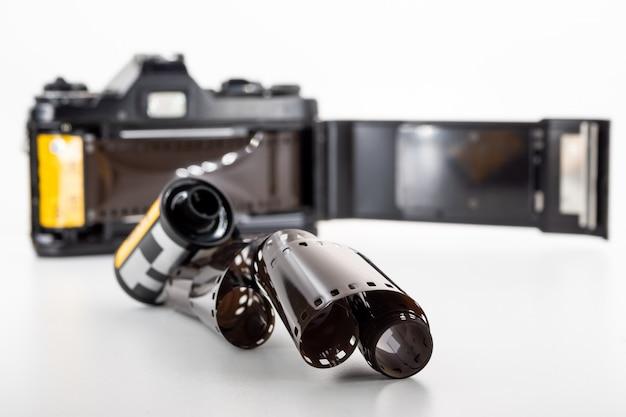 Câmera de reflexo da única lente e um rolo de filme em um fundo branco. Foto Premium