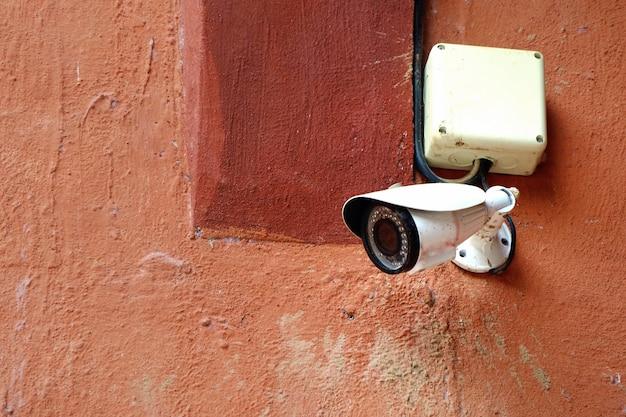 Câmera de segurança cctv no prédio da cidade com fundo de parede laranja