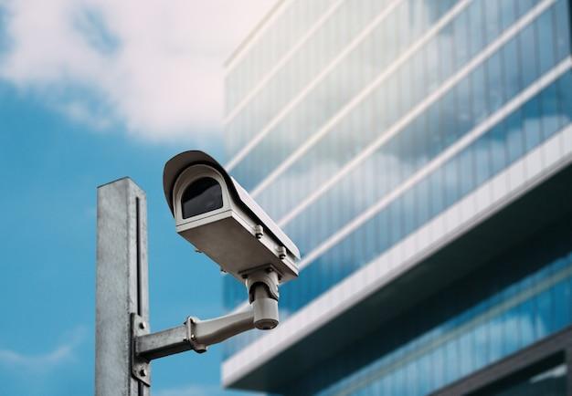 Câmera de segurança com um edifício de vidro no fundo