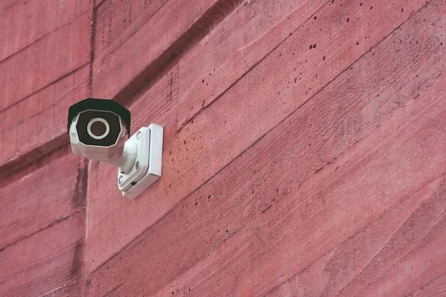 Câmera de segurança ir cctv moderna em um prédio de parede de tijolo vermelho para monitorar eventos na cidade. conceito tecnologia de vigilância e monitoramento.