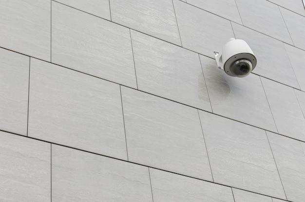 Câmera de segurança ir para monitoramento de segurança da cidade na telha de pedra cinza na parede, vista diagonal