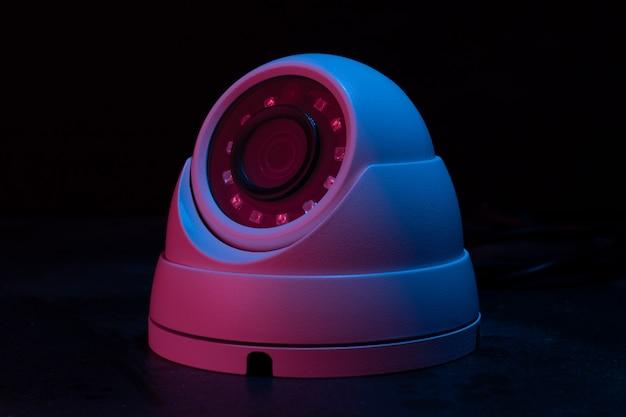 Câmera de segurança na parede escura com rosa na luz azul